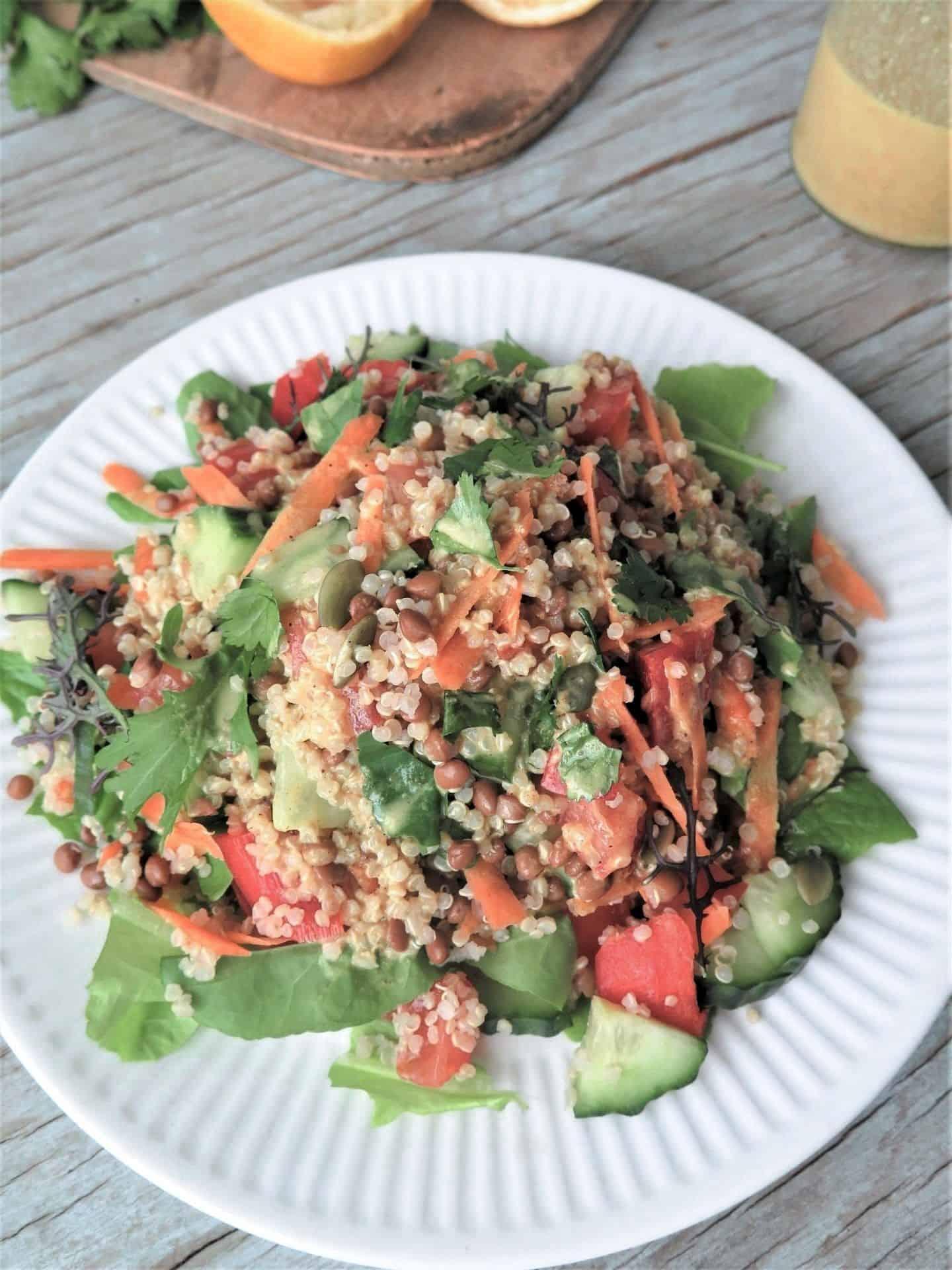 Marokkanischer Quinoa Linsen Salat, serviert auf einem Teller und Vinaigrette im Hintergrund